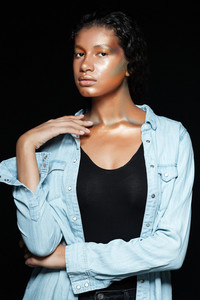 Young african model in shirt in studio. looking at camera. isolated black background