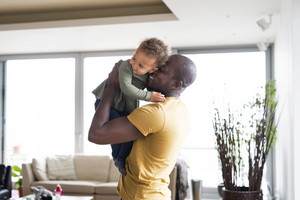 Young afro-american father with his little daughter holding her in arms at home.
