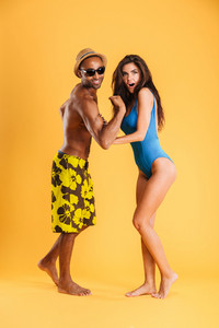 Young afro american man showing biceps to his girlfriend isolated on the orange background