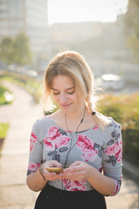 Young and beautiful blonde caucasian girl walking through the city while listening to music with earphones and a smartphone, wearing a blue and pink dress with black skirt - technology, music, serenity, relax concept