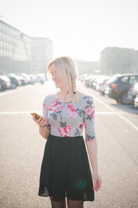 Young and beautiful blonde caucasian girl walking through the city while listening to music with earphones and a smartphone, wearing a blue and pink dress with black skirt - - technology, music, serenity, relax concept