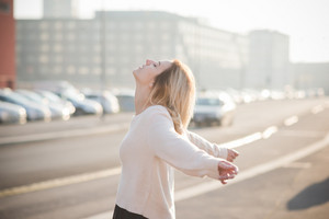 Young and beautiful blonde girl outside in the city feeling free, with arms wide open. She is wearing a white sweater and a black skirt - happiness, freedom, success concept