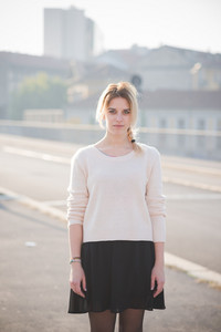 Young and beautiful blonde girl outside in the city. She is wearing a white sweater and a black skirt.