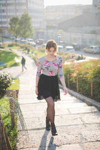 Young and beautiful caucasian blonde girl walking through the city at dusk wearing a floral dress with a black skirt.