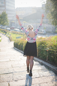 Young and beautiful caucasian blonde girl walking through the city with raised arms, at dusk wearing a floral dress with a black skirt - freedom, happiness, success concept