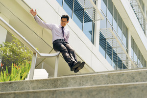 Young and happy chinese businessman sliding downstairs on rails of office staircase. The man enjoys his new promotion at job