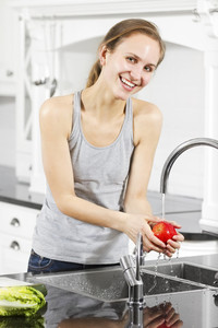 Young and natural fit / healthy / sporty woman wash / prepare vegetables and fruit. Modern and exclusive kitchen.