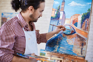 Young artist painting Italian landmark in studio