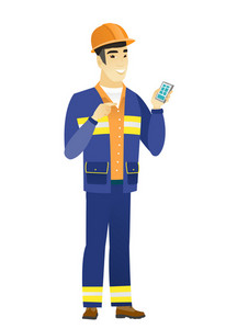 Young asian builder holding mobile phone and pointing at it. Full length of builder with mobile phone. Builder using mobile phone. Vector flat design illustration isolated on white background.