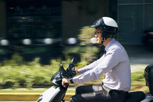Young asian businessman commuting to job. The man rides a motorcycle with white helmet. Motion blurred background