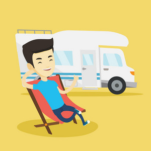 Young asian cheerful man sitting in folding chair and giving thumb up on the background of camper van. Smiling man enjoying her vacation in camper van. Vector flat design illustration. Square layout.