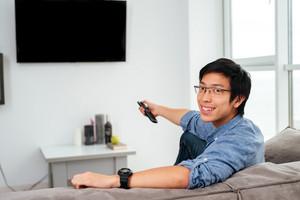 Young asian man in shirt watching tv on sofa. looking at camera