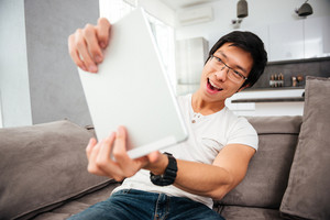 Young asian man with tablet on sofa. playing with tablet