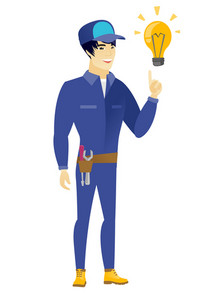 Young asian mechanic pointing at bright idea light bulb. Full length of mechanic having a creative idea. Successful idea concept. Vector flat design illustration isolated on white background.