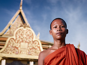 Young Asian monk smiling at camera in buddhist monastery, Phnom Penh, Cambodia, Asia. Low angle
