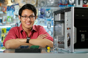 Young asian shop owner working in computer store, repairing computer and adding ram to pc. Portrait of man smiling at camera