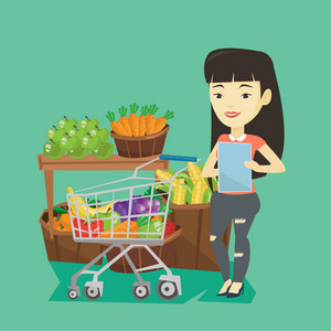 Young asian woman checking shopping list. Smiling woman holding shopping list near trolley with products. Happy woman writing in shopping list. Vector flat design illustration. Square layout.
