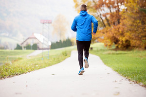 Young athlete in blue jacket running outside in colorful sunny autumn nature on an asphalt path leading through green grass. Trail runner training for cross country running.