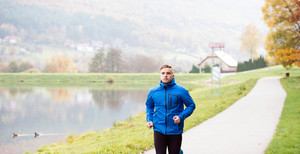 Young athlete in blue sports jacket at the lake running against colorful autumn nature