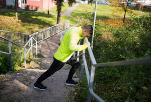 Young athlete on stairs outside in colorful sunny autumn nature, stretching legs, warming.Trail runner training for cross country race.