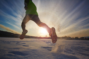 Young athlete running in snowdrift
