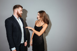 Young attracctive couple in smart wear talking to each other over gray background