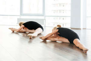 Young attractive ballet teacher and her little student doing exercises on the floor at studio