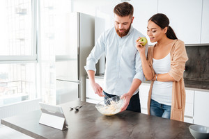Young attractive couple at home kitchen with tablet. cooked in kitchen