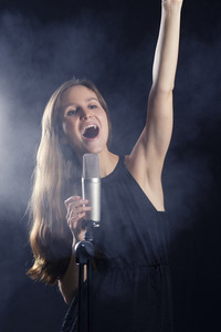 Young attractive girl sings into a microphone. Smoke and lights in the background.
