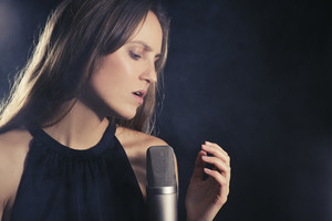 Young attractive girl sings into a microphone. Smoke in the background.