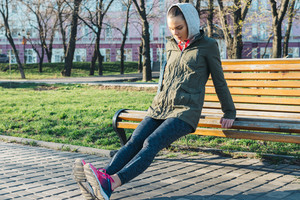 Young attractive woman doing triceps exercises in a park on a bench, morning outdoor sports