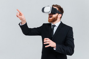 Young bearded business man in suit using virtual reality device. Isolated gray background