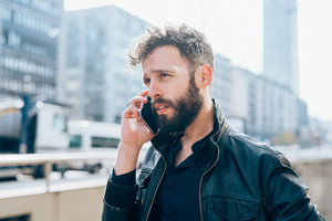 young bearded caucasian businessman talking smart phone outdoor city back light - technology, communication, business concept