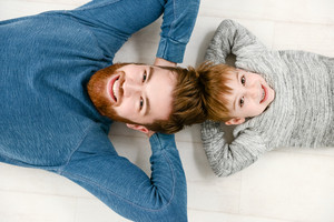 Young bearded father dressed in blue sweater lies on floor with his little cheerful son in room indoors