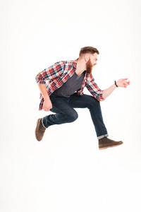Young bearded man jumping and playing on invisible guitar isolated on a white background