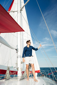 Young bearded man standing on a yacht and looking at the horizon