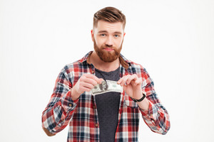 Young bearded man tearing US dollars banknotes isolated on a white background