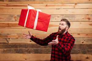 Young bearded man trying to catch gift box in motion isolated on wooden background