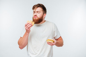 Young bearded man with eyes closed enjoying eating hamburgers isolated on white background