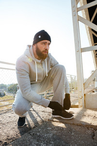Young bearded sports man athlete in hat ties his shoelaces outdoors