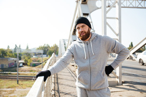 Young bearded sportsman in hat resting after workout while standing at the bridge