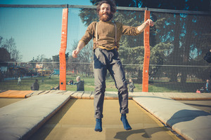 young bearded stylish handsome hipster man jumping on trampoline at playground