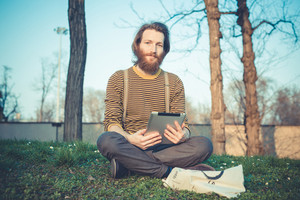 young bearded stylish handsome hipster man using tablet outdoors
