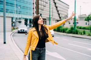 Young beautful caucasian brown long hair woman outdoor in the city hailing a taxi - transort, commuter concept