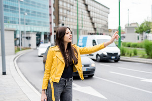 Young beautful caucasian brown long hair woman outdoor in the city hailing a taxi - transport, commuter concept