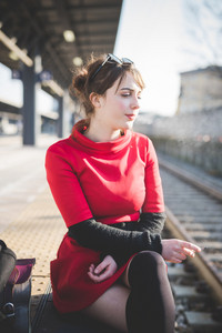 young beautidul caucasian woman smoking cigarette sitting at railway station - addiction, commuting, traveling concept