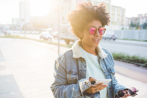 Young beautiful afro black woman holding smart phone walking outdoor in city back light wearing sunglasses - technology, social network, communication concept