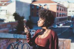 Young beautiful afro black woman outdoor in city back light listening music with headphones and smart phone hand hold - music, happiness, technology concept