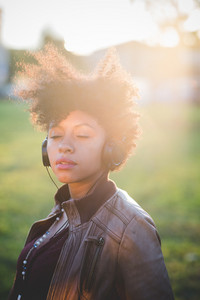 Young beautiful afro black woman outdoor in the city back light feeling free with eyes closed listening music - freedom, meditation, serenity concept