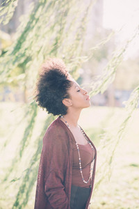 Young beautiful afro black woman outdoor in the city back light feeling free with eyes closed under a sallow tree - freedom, meditation, serenity concept